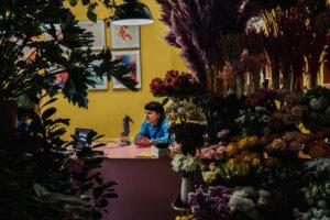 Zdjęcie przedstawia pracownię pełną kwiatów, przy stole siedzi kobieta.