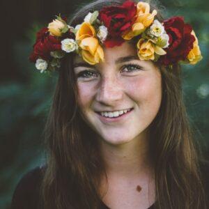Na zdjęciu jest młoda kobieta w wianku z kwiatów.