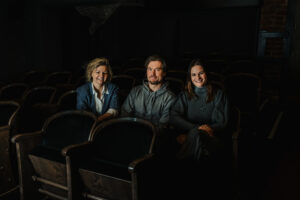 Zdjęcie przedstawia dwie uśmiechnięte kobiety - autorki podcastu - oraz mężczyznę - aktora, gościa podcastu. Wszyscy troje siedzą na starych fotelach kinowych.